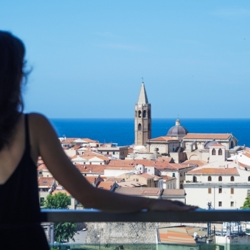 Girl looks the Alghero's downtown from the Skybar